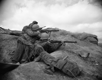 Soldiers from the USS Eldorado shoot at enemy targets at an infantry outpost during the Korean War.