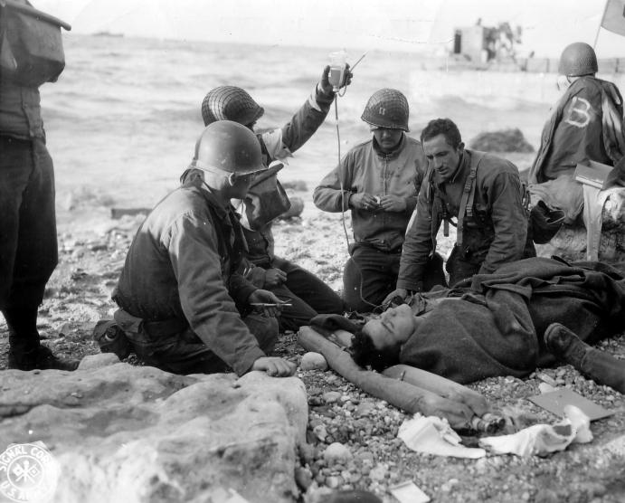 Sur la plage d'Omaha secteur Fox Green sous le Wn 60, un blessé sous perfusion attend d'être embarqué, sa tête repose sur une bouée individuelle. le 6 juin 1944 (reportage de Weintraub) infirmiers du 5th Engineer Special Brigade