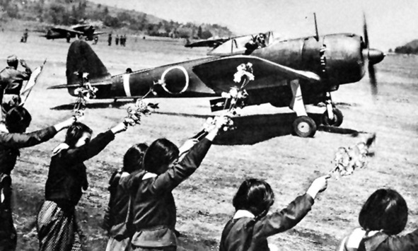 """Imperial Japanese Army Second Lieutenant Toshio Anazawa of the 20th Shimpu (Special Attack Unit) Sentai (Squadron), receives cherry blossom send-off from teenagers of Chiran Girls School as he takes off to attack American naval forces off Okinawa as part of Kikusui (swarm) number 2, the second of ten major kamikaze attacks. Cherry blossoms symbolized the Kamikazes. Anazawa is flying a Nakajima Ki-43 Hayabusa (Allied codename """"Oscar"""") fighter with 250-kilogram (551-pound) bombs. Anazawa, age 23 at the time of his death, graduated from Chuo University. Before his death, he wrote to his fiance, """"As an engaged man, as a man to go, I would like to say a little to you, a lady before I go. I only wish your happiness. Do not mind the past. You are not to live in the past. Have the courage and forget the past. You are to create a new future. You are to live from moment to moment in reality. Anazawa no longer exists in reality."""" Many kamikaze were college educated. They received little flight training, only enough to take off and maneuver, not to engage in aerial combat. The Nadeshiko Unit, made up of high school girls, helped with maintenance at the Chiran Air Base, where many kamikaze took off on suicide missions against the American fleet off Okinawa. Chiran also was the residence of Tome Torihama, a mother of two who ministered to the kamikaze pilots in the Tomiya eatery. She smuggled letters home, cooked their last meals, and hugged them goodbye. She led a movement to rehabilitate the reputation of the kamikaze and established a memorial in Chiran. In the two month battle for Okinawa, the Imperial Japanese Army and Navy flew 1,900 kamikaze missions, sinking dozens of allied ships and killing more than five thousand U.S. sailors."""